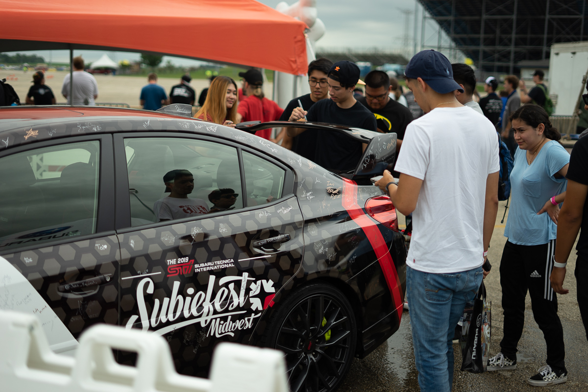 Attendees signing the WRX for charity